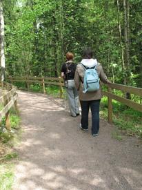 Luontopolku, jota kulkee kaksi henkilöä peräkkäin. He pitävät kiinni oikealla olevasta käsijohteesta.