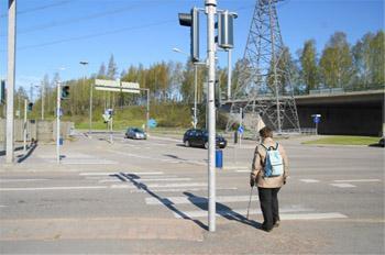 Nainen lähestyy suojatietä, jossa on liikennevalot.