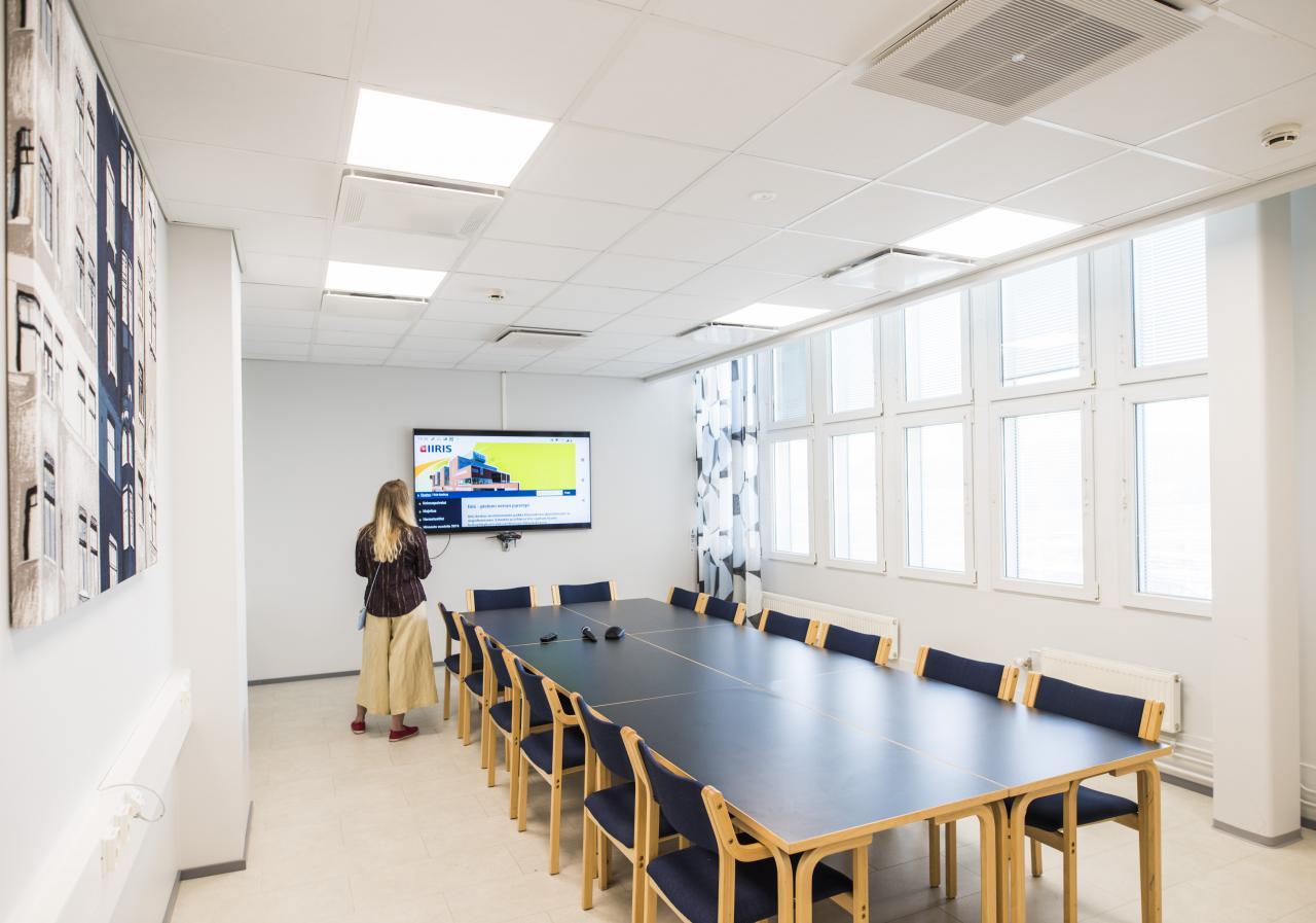 Kokoushuone, valkoiset seinät, pöydässä tuolit 12 henkilölle, taustalla televisionäyttö ja valoisat ikkunat.