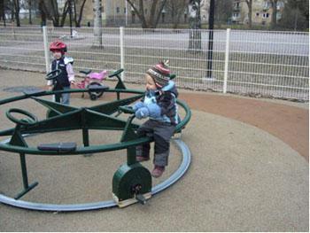 Kaksi lasta, toinen istuu leikkipuiston karusellissa ja toinen seisoo sen vierellä.