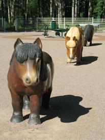 Kolme puista ponia lasten leikkipuistossa.