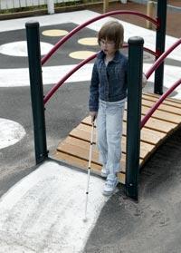 Lapsi kävelee valkoisen kepin kanssa leikkipuiston sillalla, asfaltissa valkoista maalia.