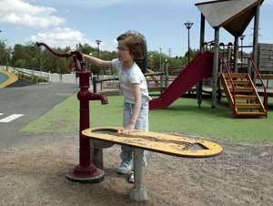 Lapsi leikkipuistossa vesipumpun ääressä.