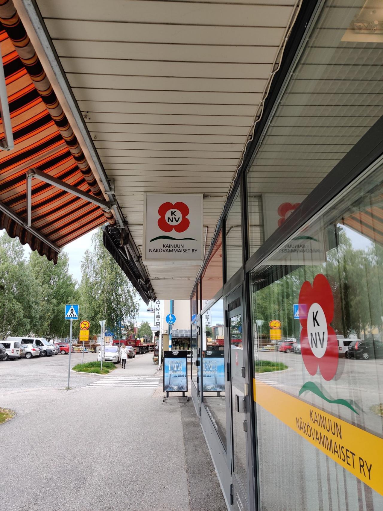 Kainuun Näkövammaiset toimiston etuoven yllä oleva kyltti, jossa yhdistyksen logo.