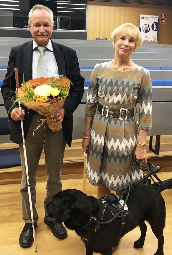 Mies valkoisen kepin ja kukkakimpun kanssa ja nainen, jolla musta opaskoira. Molemmat hymyilevät.