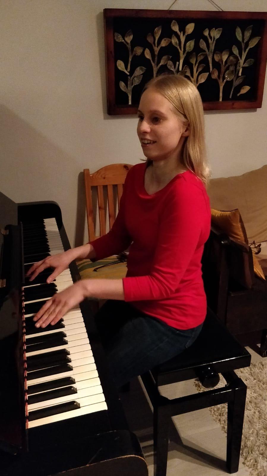 Minja soittaa pianoa ja hymyilee.