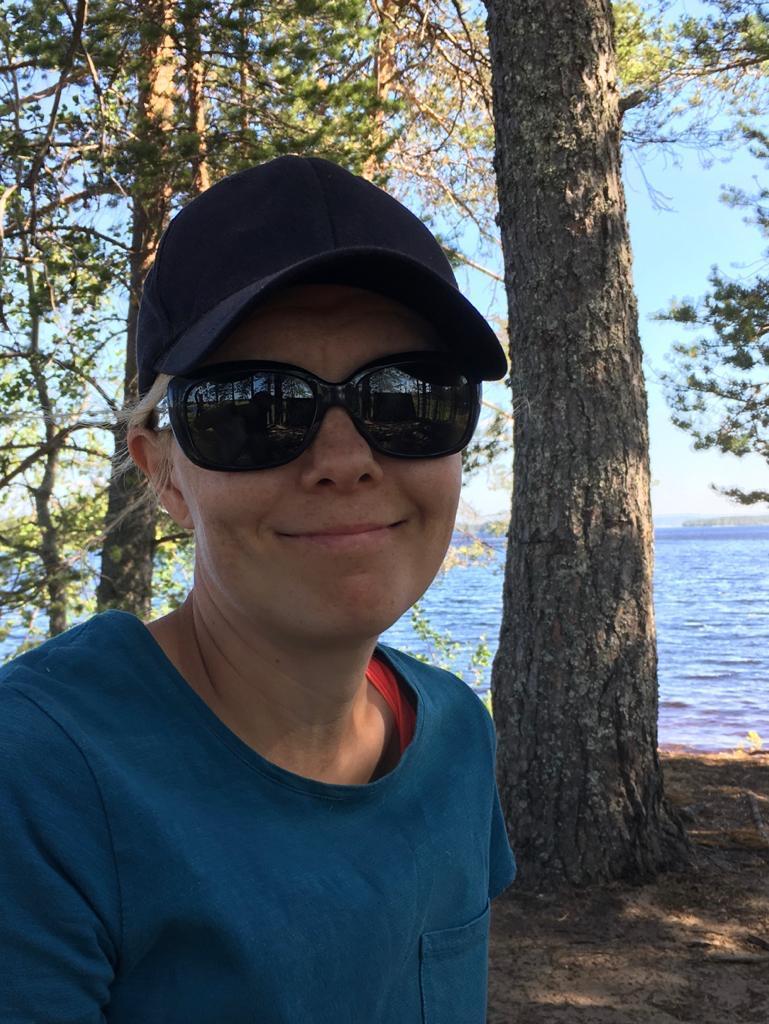 Maija katsoo hymyillen kameraan kesäisessä järvimaisemassa. Päässään hänellä on aurinkolasit ja lippalakki.