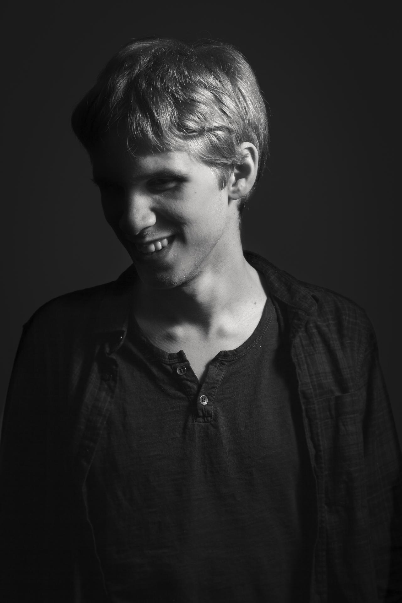 Mustavalkoinen kuva, jossa Tuukka katsoo hymyillen vasemmalle alas.