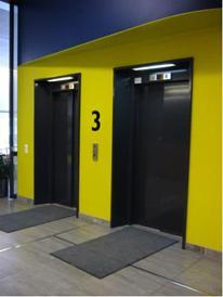 Keltainen seinä, jonka keskellä kaksi mustaovista hissiä ja iso numero 3. Molemmille hissinoville johtaa tumma lista.