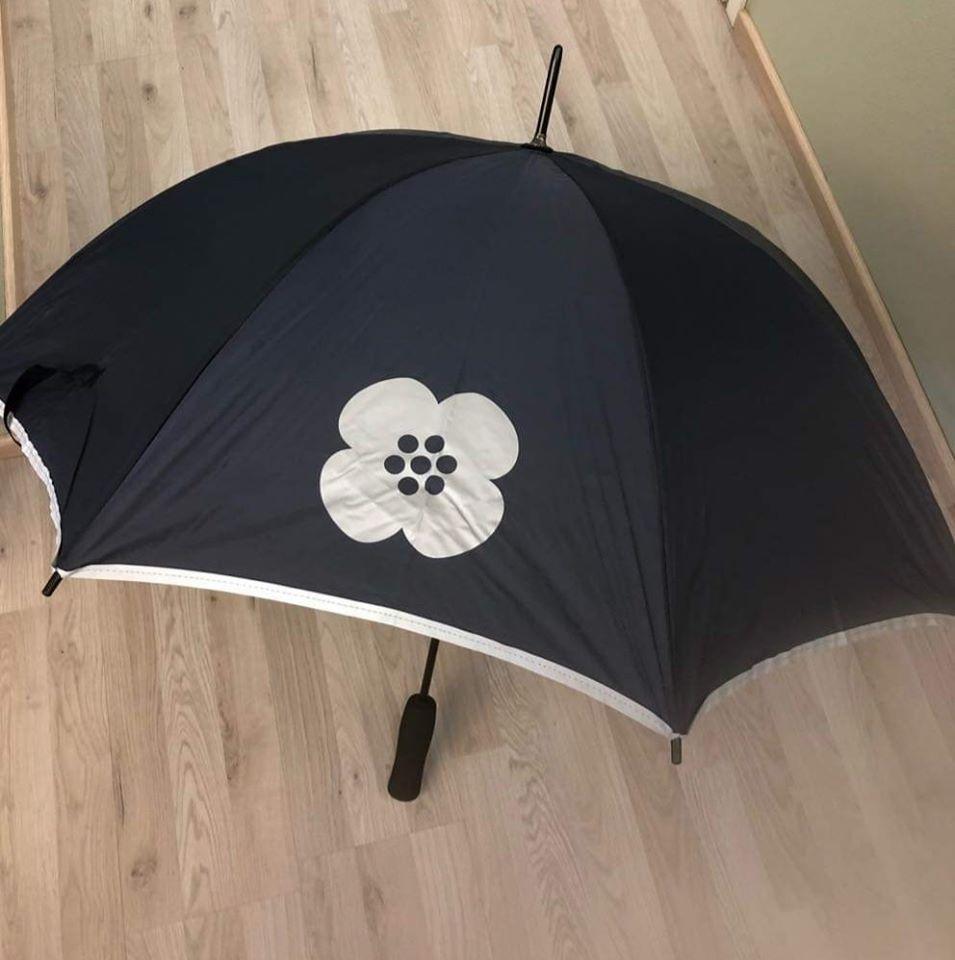 Lattialle avattu tummansininen sateenjvarjo, jossa annansilmäkukka.