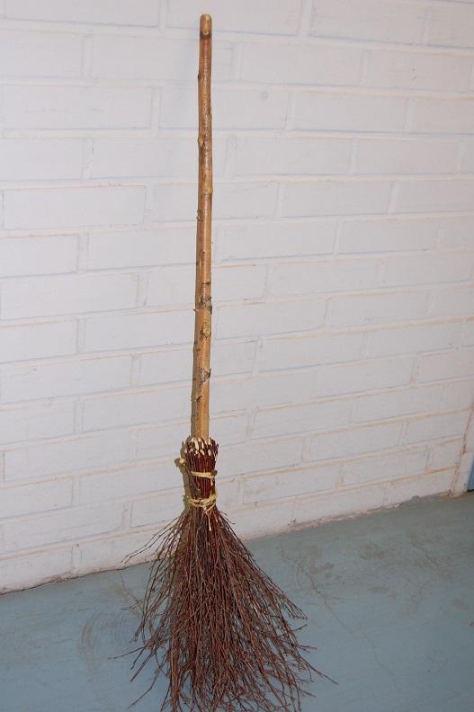 Kuvassa on valmis risuluuta, jossa on pitkä puinen varsi.