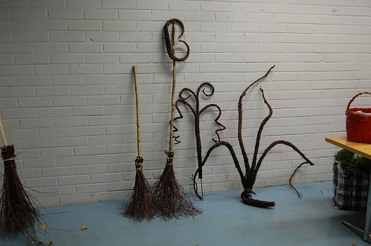 Kuvassa on kaksi varrellista risuluutaa, jotka nojaavar tiiliseinää vasten. Kuvassa myös puiden oksista tehtyjä koriste-esineitä risuluutien vieressä.