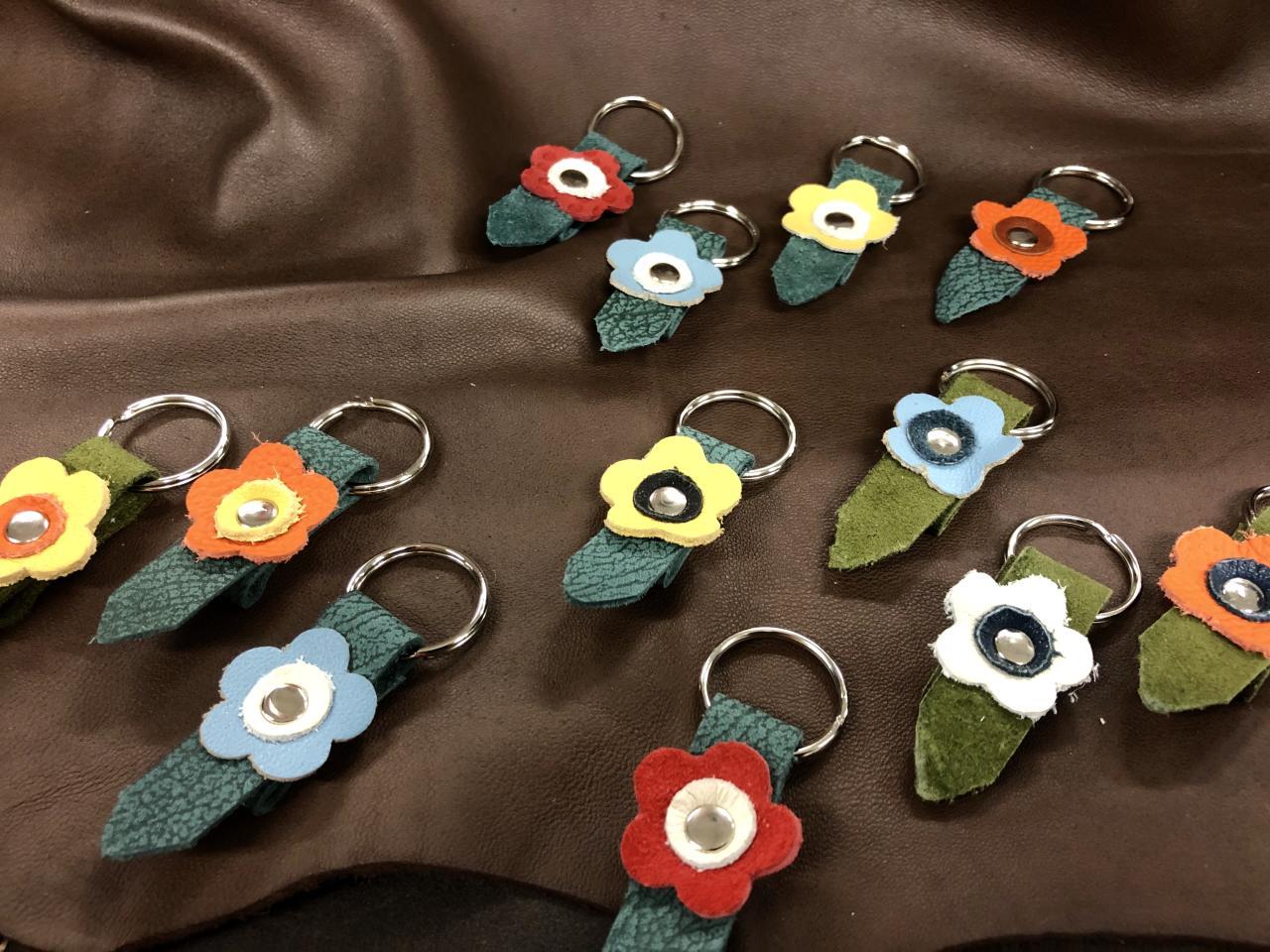Erivärisistä nahoista tehtyjä kukan muotoisia avaimenperiä.