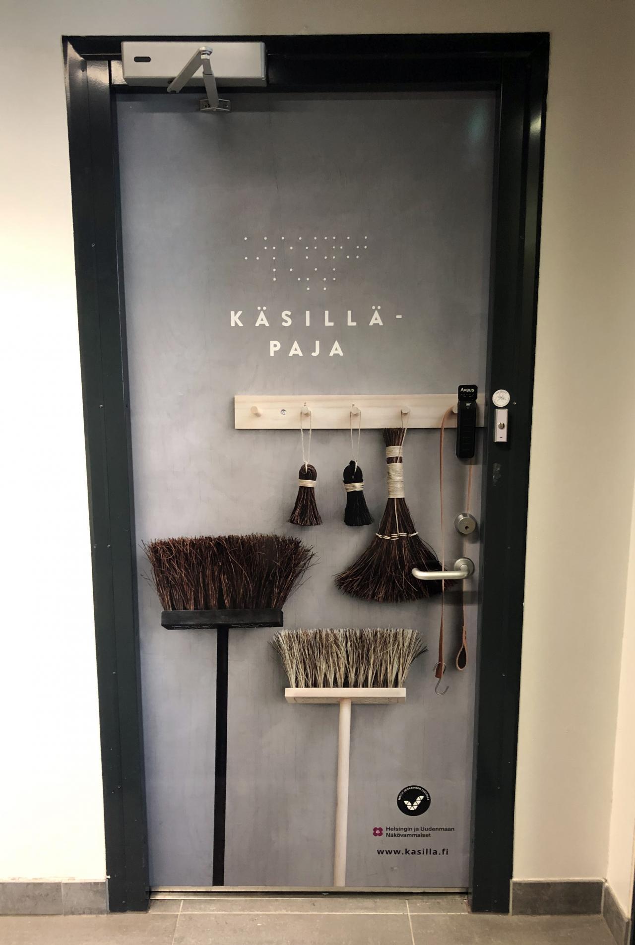 Kuva-aiheella teipattu Käsillä-pajan ovi: ovessa on erilaisia harjoja, joiden yläpuolella lukee Käsillä-paja.