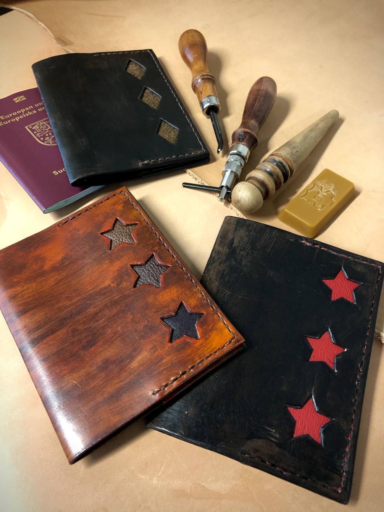 Nahasta valmistettuja passikoteloita, joissa intarsiatekniikalla tehtyjä tähti- ja salmiakkikuvioita. Taustalla nahkatyökaluja.