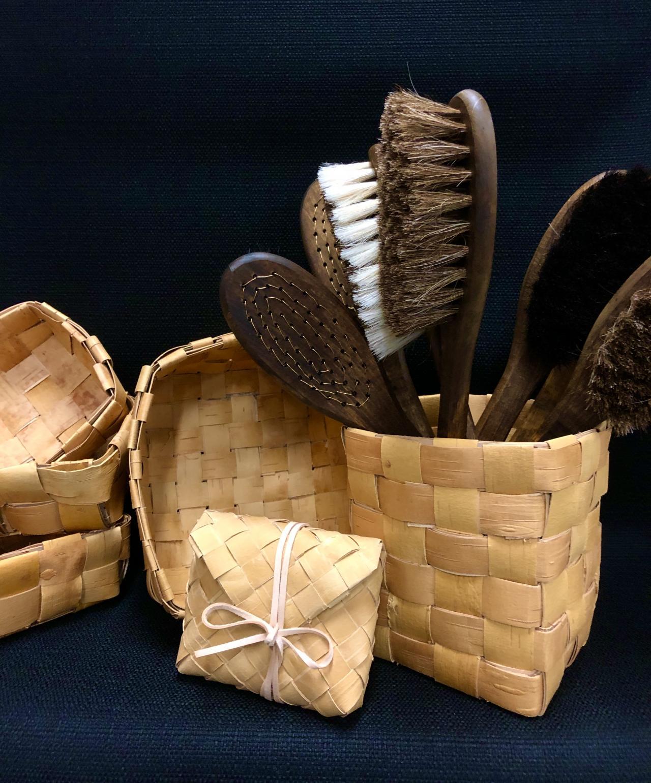 Kirjekuorimallinen tuohikukkaro ja suorapunontaisia tuohikoppia, joissa yhdessä somisteena saunaharjoja.