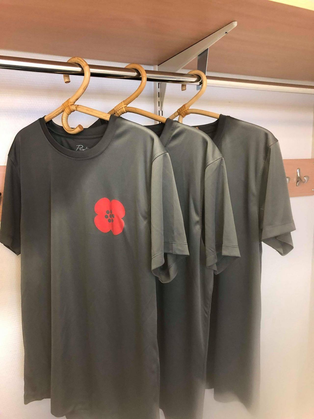 3 harmaata t-paitaa henkareissa naulakossa, paidan rinnassa punainen annansilmä-kukka.