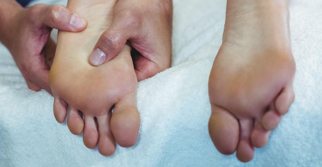 Hoitaja käsittelee vatsamakuulla makaavan asiakkaan paljaita jalkapohjia.