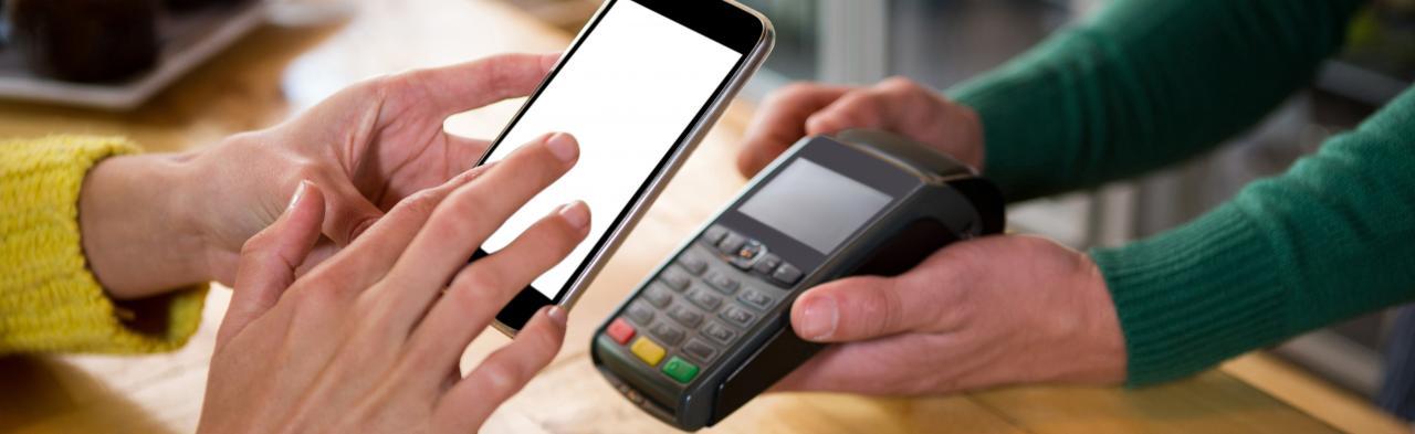 Asiakas hoitaa maksua kännykällään hoitajan pidellessä maksupäätettä käsissään.
