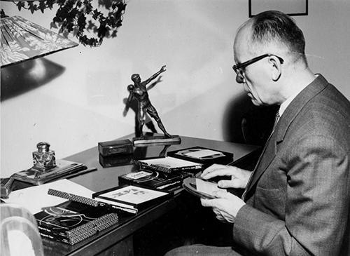 Sokeain Keskusliiton ensimmäinen puheenjohtaja Einar Juvonen. Hän istuu kirjoituspöydän ääressä ja pöydällä on useampia äänikirjoja. Juvonen pitää kädessään yhtä ääninauhaa.