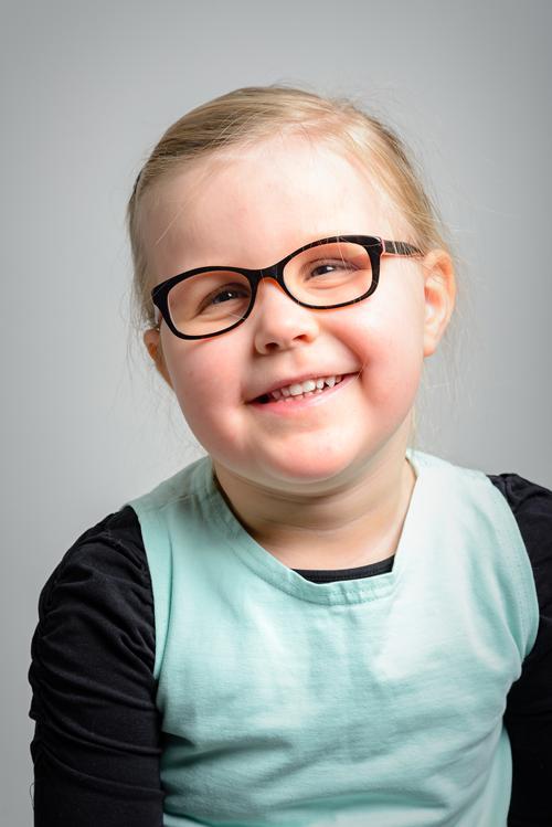 Muotokuva 4-vuotiaasta hymyilevästä silmälasipäisestä tytöstä. Tytöllä on vaaleat hiukset poninhännällä ja tummasankaiset silmälasit. Hänellä on vaalean turkoosin värinen tunika ja musta pitkähihainen aluspaita.