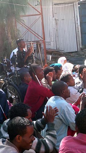 Maassa istuu joukko etiopilaisia nuoria naisia ja miehiä. Taustalla näkyy peltivaja sekä puu. Keskellä on näkövammainen mies, jolla on kirkkaanpunainen paita ja valkoinen keppi kainalossa.
