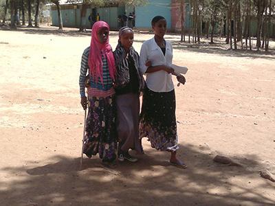 Kolme nuorta etiopialaisnaista kävelevät vierekkäin hiekkatiellä. Taustalla näkyy puita ja sininen talo.