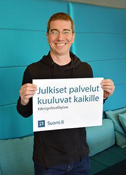 """Jani Ruuskanen seisoo turkoosin seinän edessä, hänellä on silmälasit, lyhyt tumma tukka ja musta paita. Hän pitelee käsissään kylttiä, jossa lukee """"Julkiset palvelut kuuluvat kaikille, #designforallbylaw, Suomi.fi""""."""