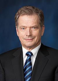 Tasavallan presidentti Sauli Niinistö, jolla on päällään tumma puku ja sininen solmio. Hänellä on vaaleanruskeat hiukset ja hän hymyilee.