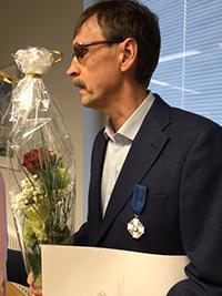 Teuvo Heikkosen puvun vasempaan rintapieleen on kiinnitetty Suomen valkoisen ruusun ritarimerkki ja hänellä on kädessään kukkakimppu.