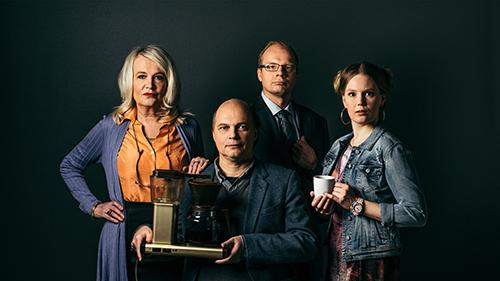 Neljä näyttelijää vierekkäin. Edessä keskellä oleva pitää käsissään MoccaMaster-kahvinkeitintä, ja hänen vieressään olevalla on valkoinen kahvikuppi kädessään.