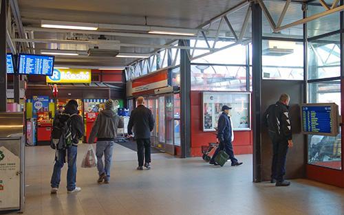 Kuva Itäkeskuksen metroasemalta. Mies katsoo läheltä pään korkeudella olevaa aikataulunäyttöä kuvan oikeassa reunassa. Vasemmassa reunassa vastaava näyttö on korkealla.