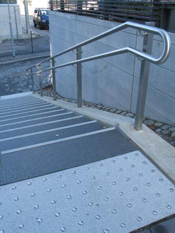 Alaspäin menevät portaat, joissa on huomiolaatta varoittamassa portaiden alkamisesta.