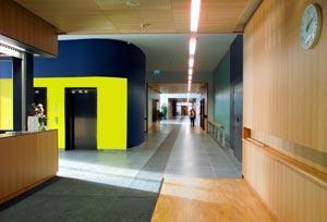 Iiriksen aula, josta johtaa pitkä käytävä suoraan eteenpäin. Vasemmalla on infotiski sekä hissit.