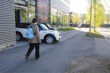 Nainen kulkee jalkakäytävällä. Hänen eteensä ajaa valkoinen henkilöauto parkkihallista.