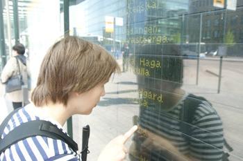 Nainen katsoo bussikaikatauluja lasin takaa. Lasi on hyvin heijastava.