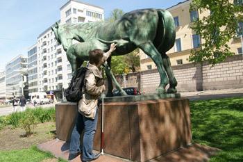 Nainen koskettaa patsasta, jossa on hevonen ja sen varsa.