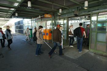 Nainen on astumassa sisään metroasemalle. Hänen ympärillään on paljon muita matkustajia.