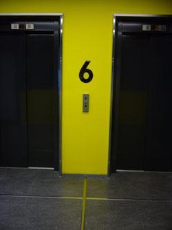 Kahden hissin välissä on keltaisella seinällä hyvin erottuva musta numero kuusi, joka kertoo kerroksen.