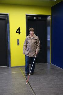 Nainen tulee hissistä ulos ja lähtee seuraamaan ohjausraitaa.