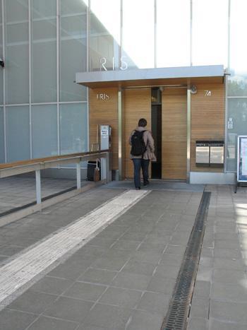 Naishenkilö kulkee Iiris-keskuksen pääsisäänkäynnistä sisään. Ovet ovat puunväriset automaattiovet.