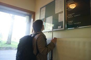 Nuori nainen lukee rappukäytävässä olevia tiedotteita.