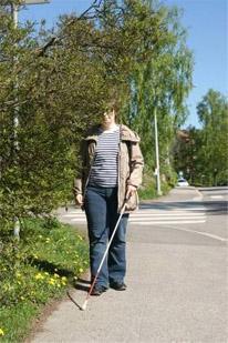 Nainen kävelee suojatiellä ja törmäämässä alhaalla roikkuviin oksiin.