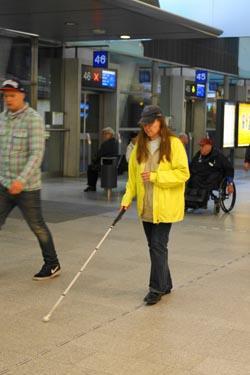 Keltaiseen takkiin pukeutunut nainen seuraa ohjausraitaa valkoisella kepillä.