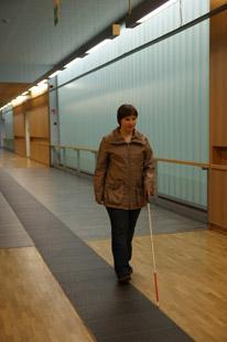 Nainen kulkee valkoisen kepin kanssa leveällä käytävällä.