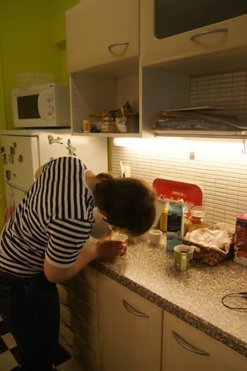 Nuori nainen kaataa vedenkeittimestä vettä kuppiin keittiössä.