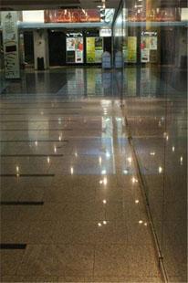 Kiiltävä lattiapinta, josta peilautuu valoja.