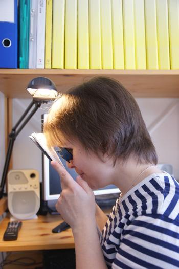 Nuori nainen lukee lehteä luupin avulla.