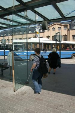 Nainen kävelee kohti bussipysäkillä olevaa lasiseinää.