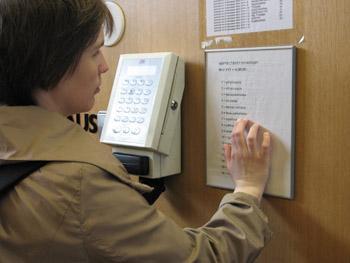 Nainen lukee pistekirjoitustaulua, joka on työaikapäätteen vieressä.